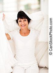 middle aged woman having fun with duvet