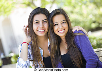 Happy Mixed Race Young Adult Female Friends Portrait Outside on Bench.