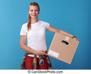 happy modern woman in white shirt holding cardboard box on blue