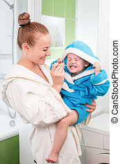 Happy mother and child teeth brushing together in bathroom