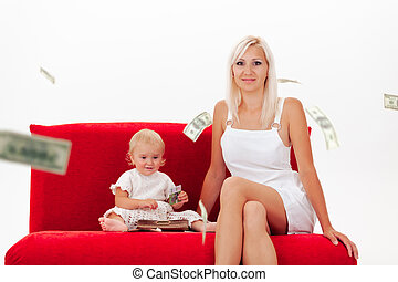 happy mother and daughter in white clothes sit on sofa in the rain of dollars
