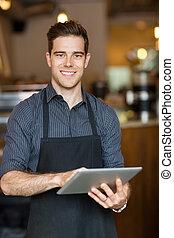 Happy Owner Holding Digital Tablet In Cafe