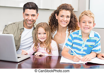 Happy parents colouring and using laptop with their young children at home in kitchen