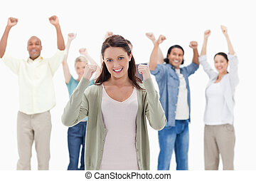 Happy people raising their arms focus on the woman in foreground