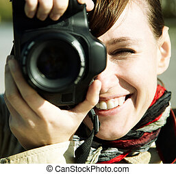 Happy young woman with camera, toned, focus point on eye