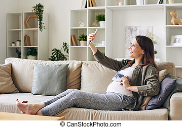 Happy pregnant woman with ultrasonic picture of her baby making selfie on couch
