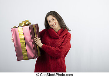 Happy pretty young woman holding gift box over white background
