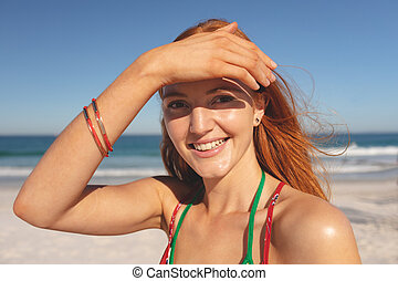 Happy redhead woman standing on the beach