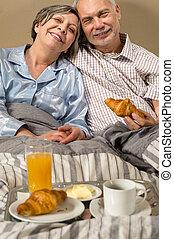 Happy retired couple eating croissant breakfast