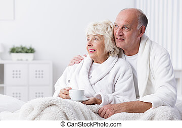 Happy retired couple in bed