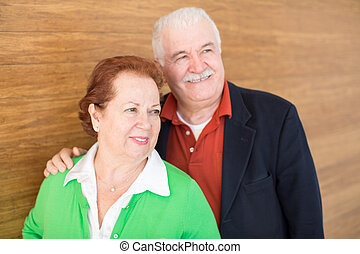 Happy Retired Couple on Wooden Wall Background