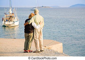 Senior couple is watching sailboats off the coast of Croatia