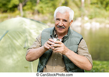Happy senior active man with hot drink looking at you while enjoying his trip