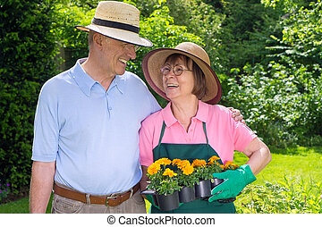 Happy Senior Couple in Garden with Flat of Flowers