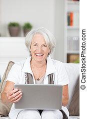 Happy senior lady using a laptop computer