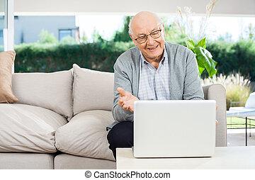 Happy Senior Man Video Chatting On Laptop At Porch