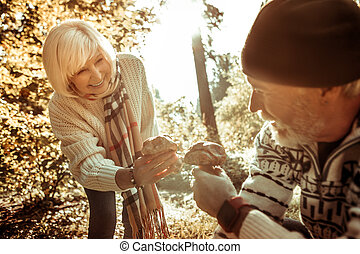 Happy senior woman gathering mushrooms with her husband.