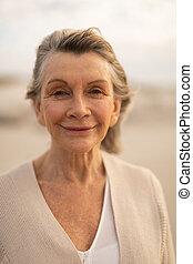 Happy senior woman standing on the beach