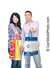 Happy shoppers couple give bags