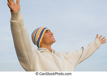 happy smiling hispanic young man arms raised in faith