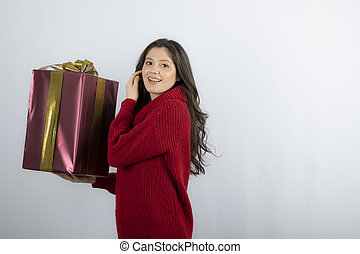 Happy woman holding a Christmas present with ribbon
