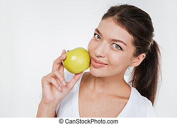 Happy woman holding apple near face