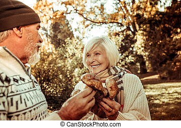 Happy woman holding mushrooms and looking at her husband.
