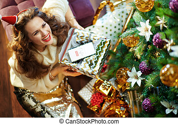happy woman holding torn christmas present box with coffee