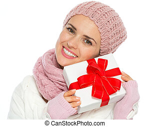 Happy woman in knit winter clothing holding Christmas present box