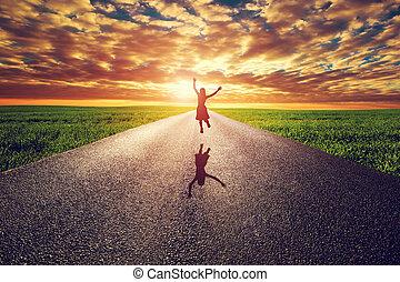 Happy woman jumping on long straight road, way towards sunset sun