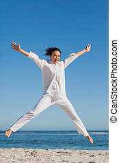 Happy woman jumping on the beach