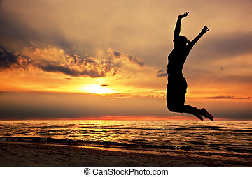 Happy woman jumping on the beach at sunset