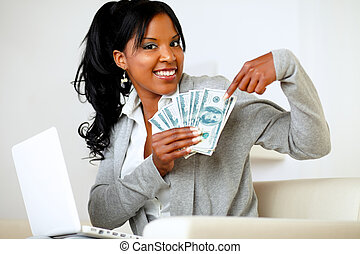 Happy woman pointing plenty of cash money