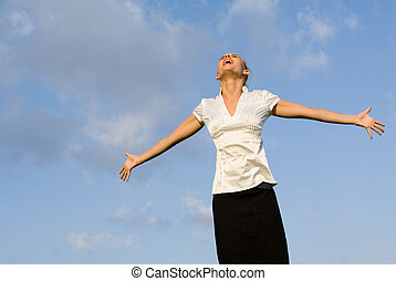 happy woman singing outdoors, looking up arms outstretched