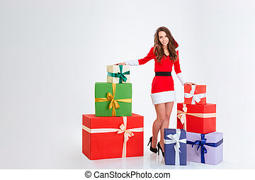 Happy woman standing with many present boxes