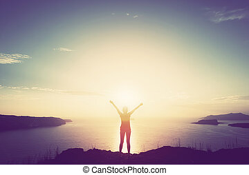 Happy woman with hands up on cliff over sea and islands at sunset