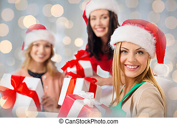 happy women in santa hats with christmas gifts