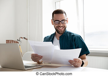 Happy young businessman in glasses looking through paper documents.