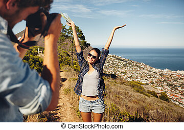 Happy young couple taking pictures while hiking