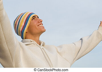 Happy young man arms raised in praise