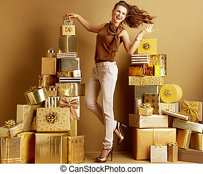 happy young shopper woman holding golden bow on top