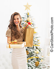 Happy young woman christmas present boxes in front of christmas tree