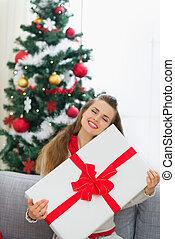 Happy young woman embracing big Christmas present box