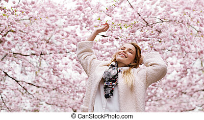 Happy young woman enjoying fresh air at spring blossom park