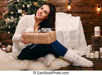 Happy young woman giving christmas present box