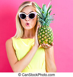 Happy young woman holding a pineapple