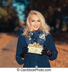 Happy young woman holding a small present box. Happy and positive young blond woman with a gift on outdoor autumn