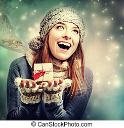 Happy young woman holding a small present box