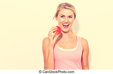 Happy young woman holding apple