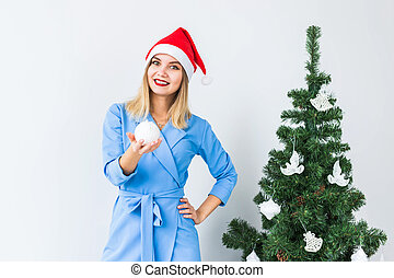 Happy young woman holding Christmas ball in front of Christmas tree.